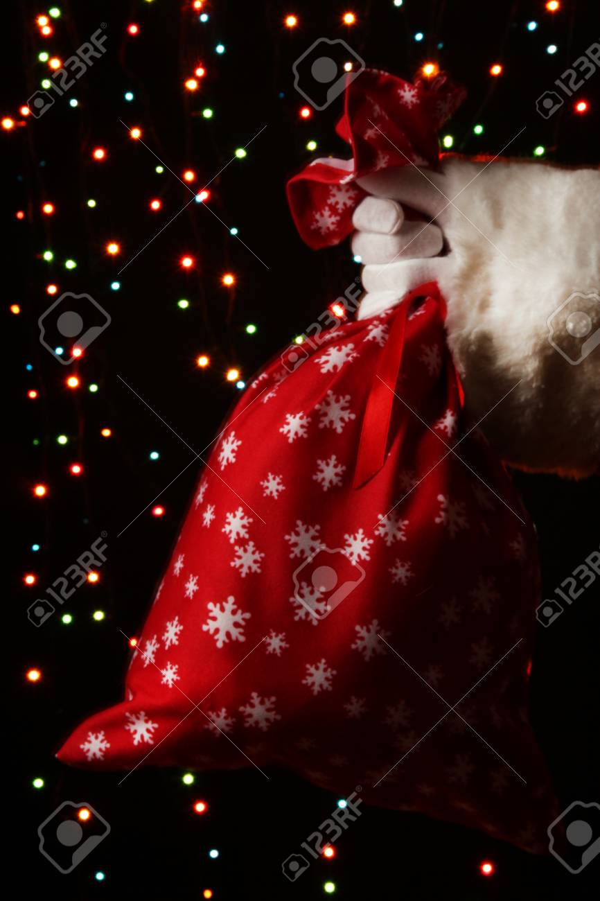 Santa Claus hand holding bag of gifts on bright background Stock Photo - 16342537