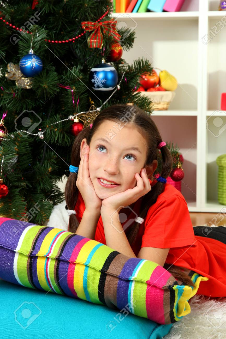 Little girl dreaming near christmas tree Stock Photo - 17129813