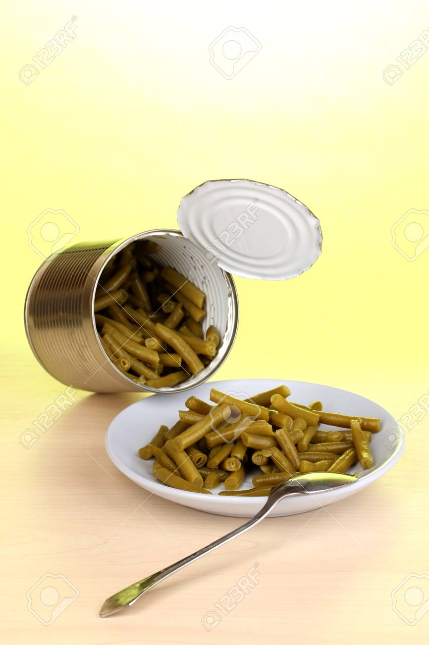 Open tin can and plate with french bean and spoon on wooden table on green background Stock Photo - 16495452