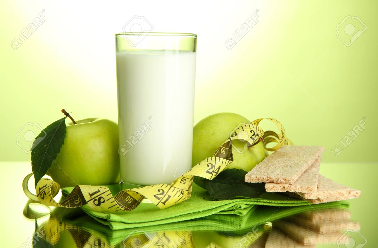 Glass of kefir, apples, crispbreads and measuring tape, on green background Stock Photo - 16591996