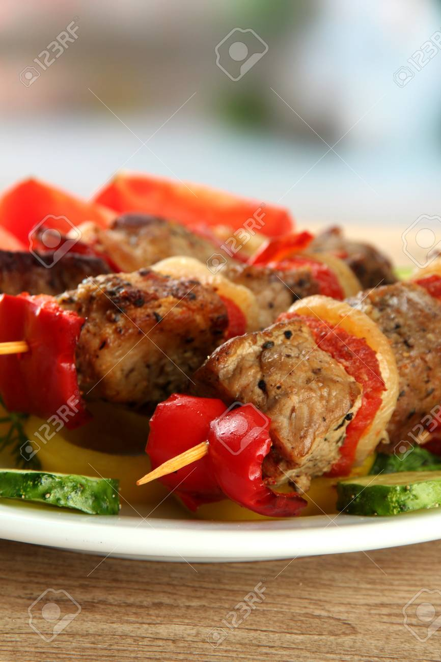 tasty grilled meat and vegetables on skewer on plate, on wooden table Stock Photo - 16620567