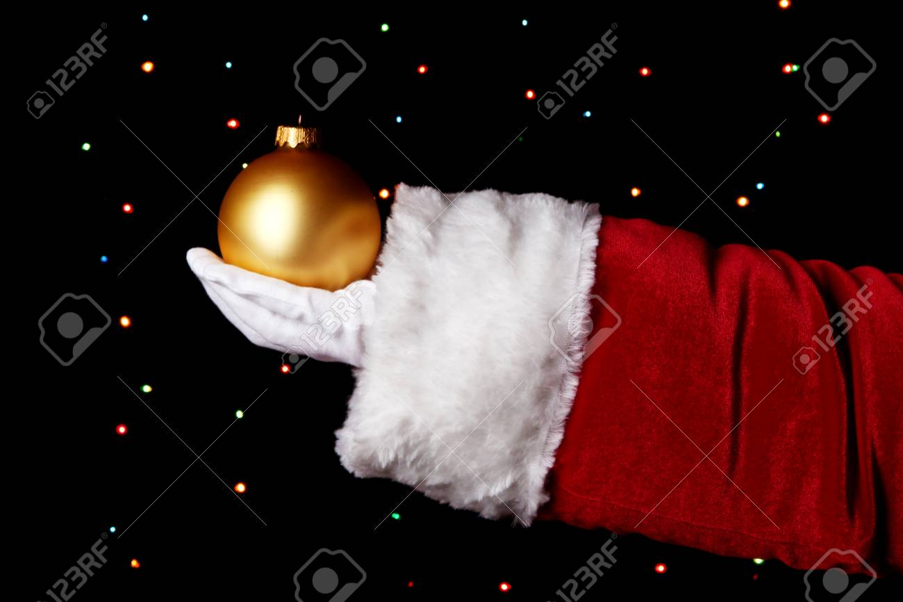 Santa Claus hand holding christmas ball on bright background Stock Photo - 16737073