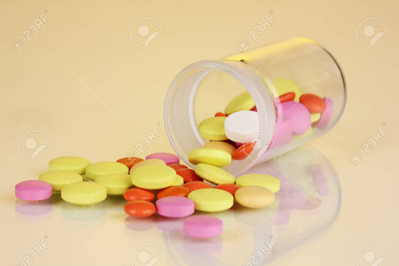 Pills in receptacle on yellow background Stock Photo - 16938628