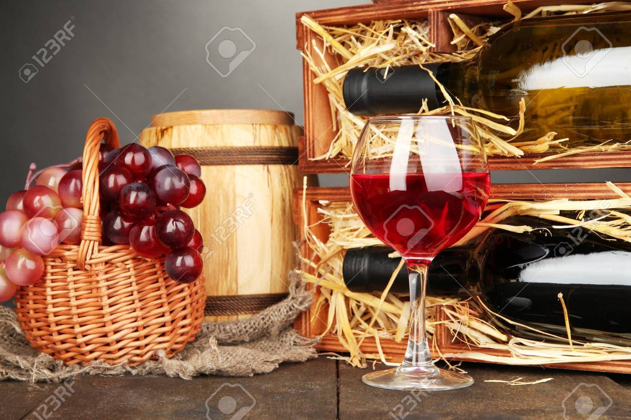 Wooden case with wine bottles, barrel, wineglass and grape on wooden table on grey background Stock Photo - 16938938