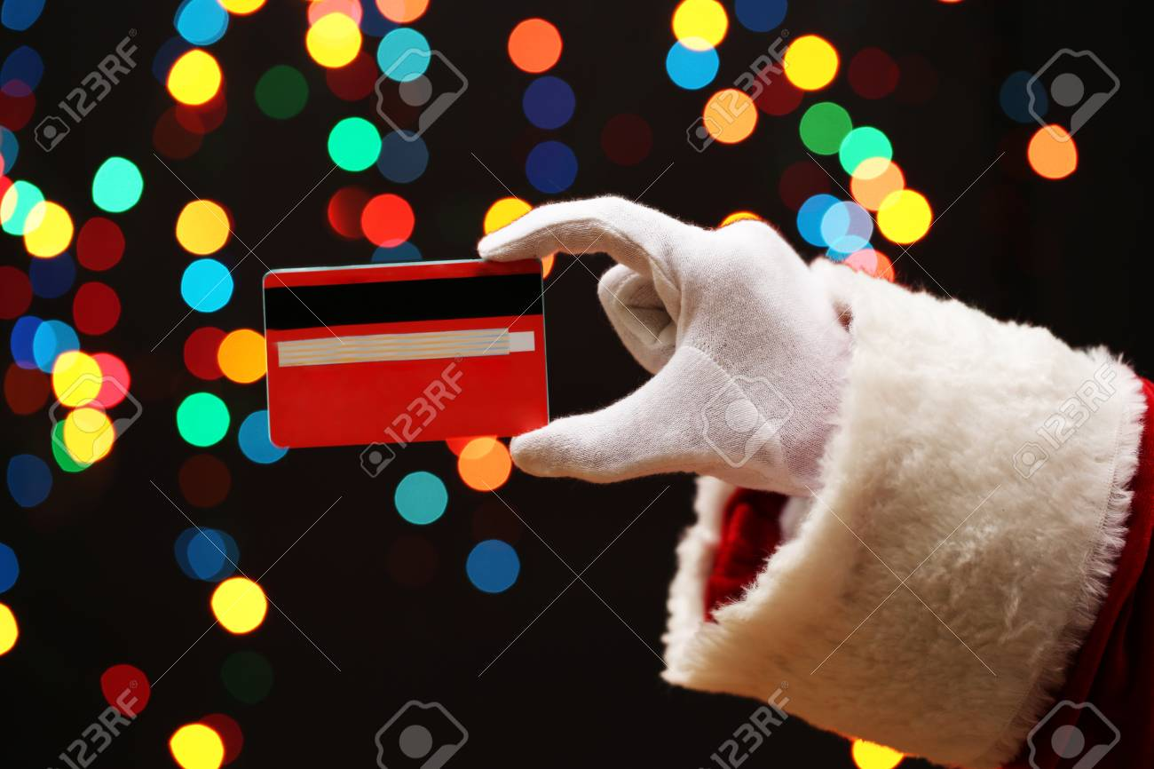 Santa Claus hand holding credit card, on garland background Stock Photo - 17000694