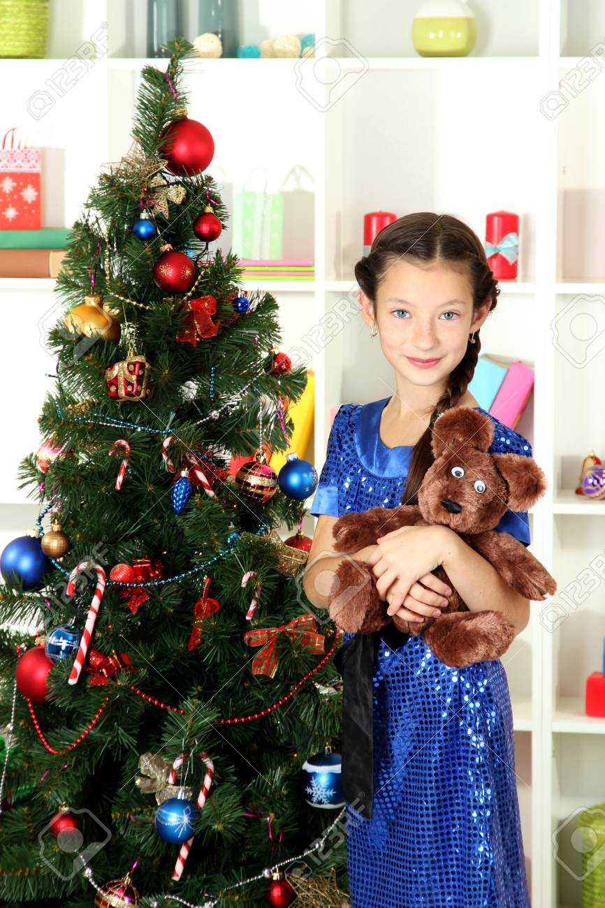 Little girl holding toy near christmas tree Stock Photo - 17186448