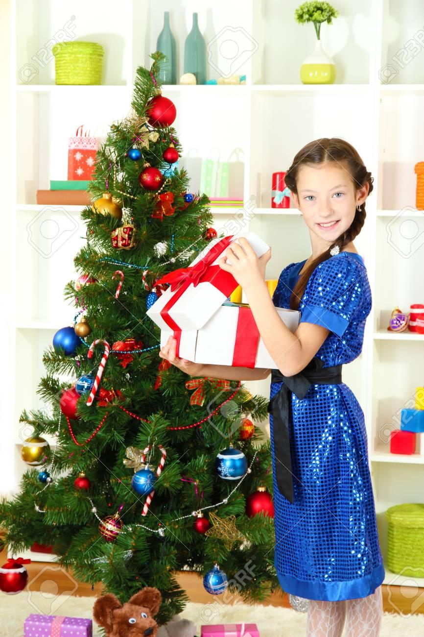 Little girl holding gift box near christmas tree Stock Photo - 17129346