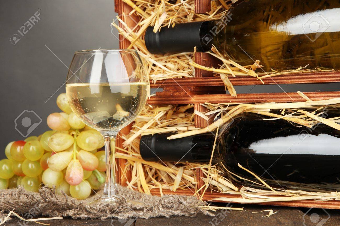 Wooden case with wine bottles, wineglass and grape on wooden table on grey background Stock Photo - 17054610