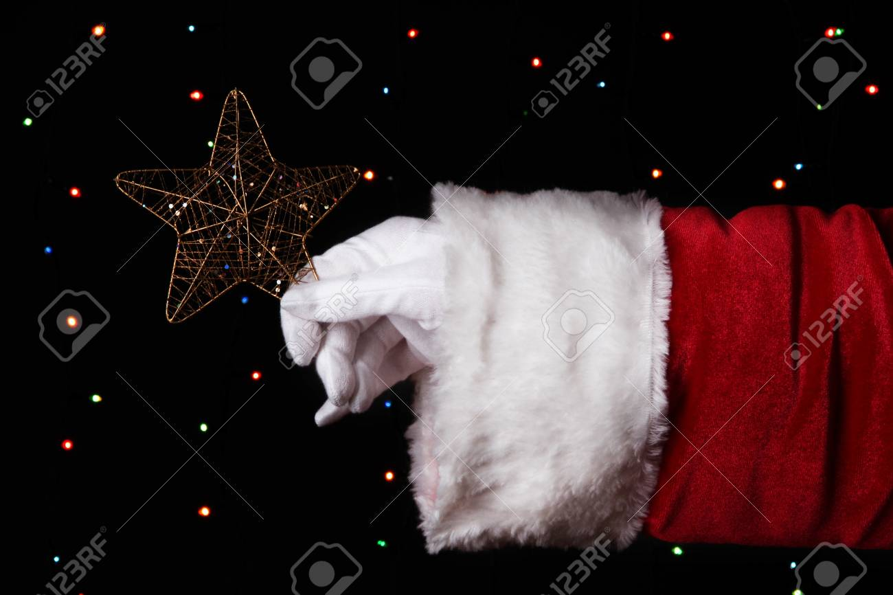 Santa Claus hand holding christmas star on bright background Stock Photo - 17064444