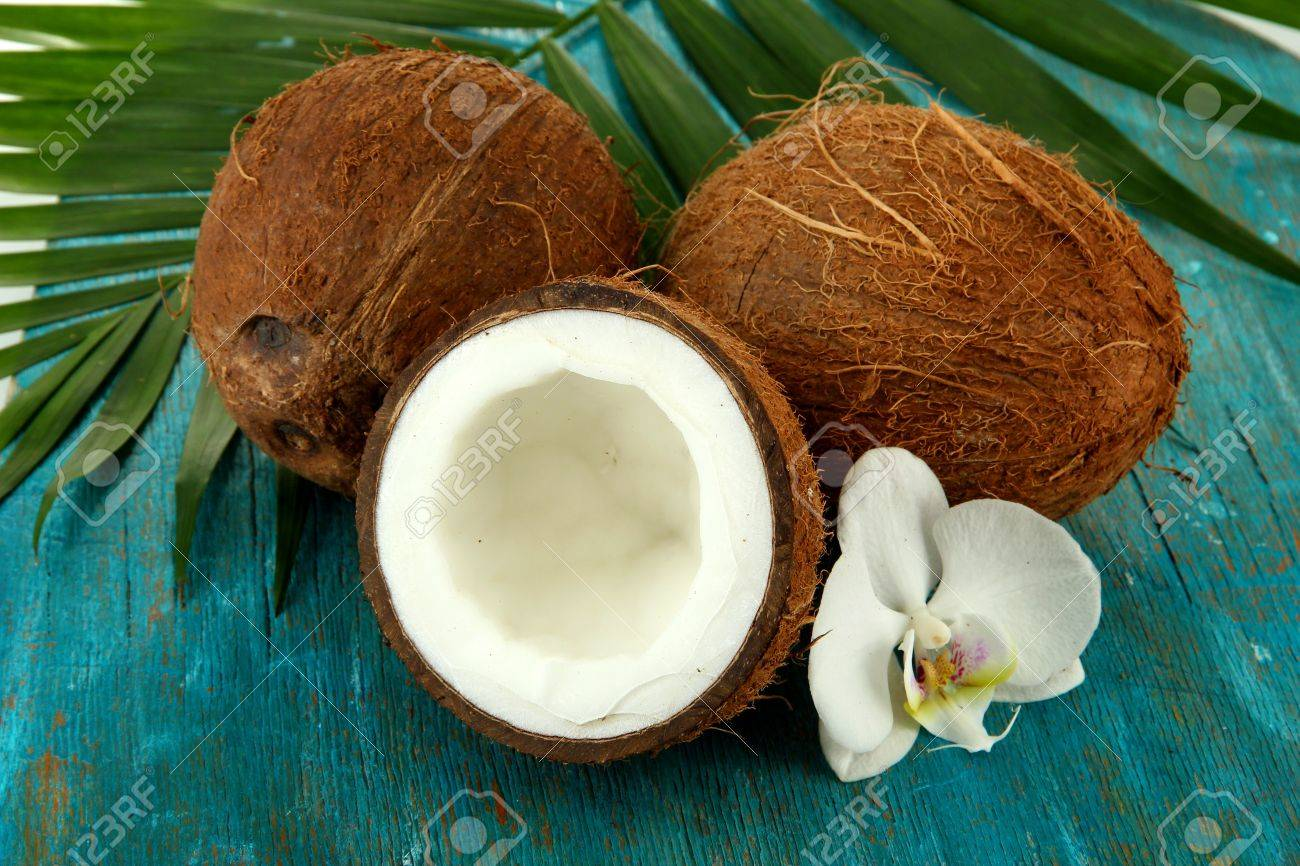Coconuts with leaves and flower, on blue wooden background Stock Photo - 17086875