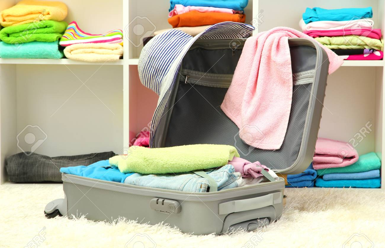 Open silver suitcase with clothing in room Stock Photo - 17111197