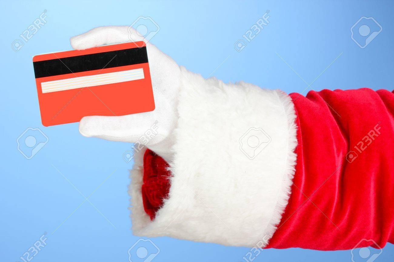 Santa Claus hand holding red credit card on blue background Stock Photo - 17187918