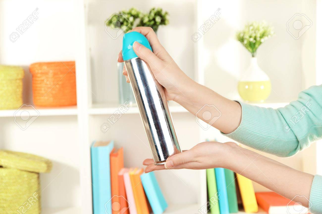 Sprayed air freshener in hand on white shelves background Stock Photo - 17245825