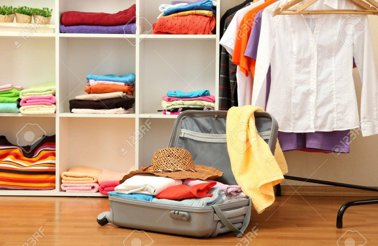 Open silver suitcase with clothing in room Stock Photo - 17265730