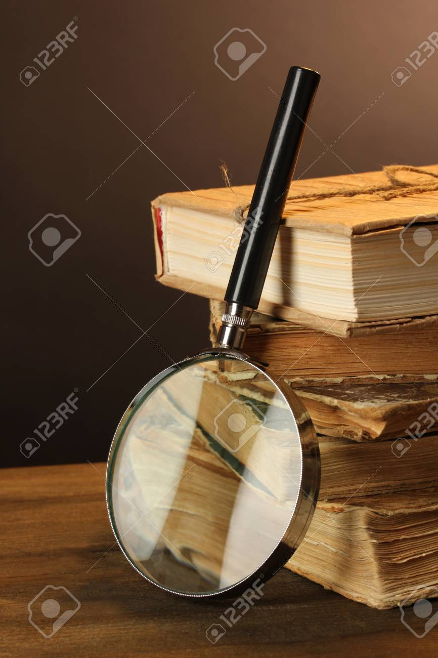 Magnifying glass and books on table Stock Photo - 17321707