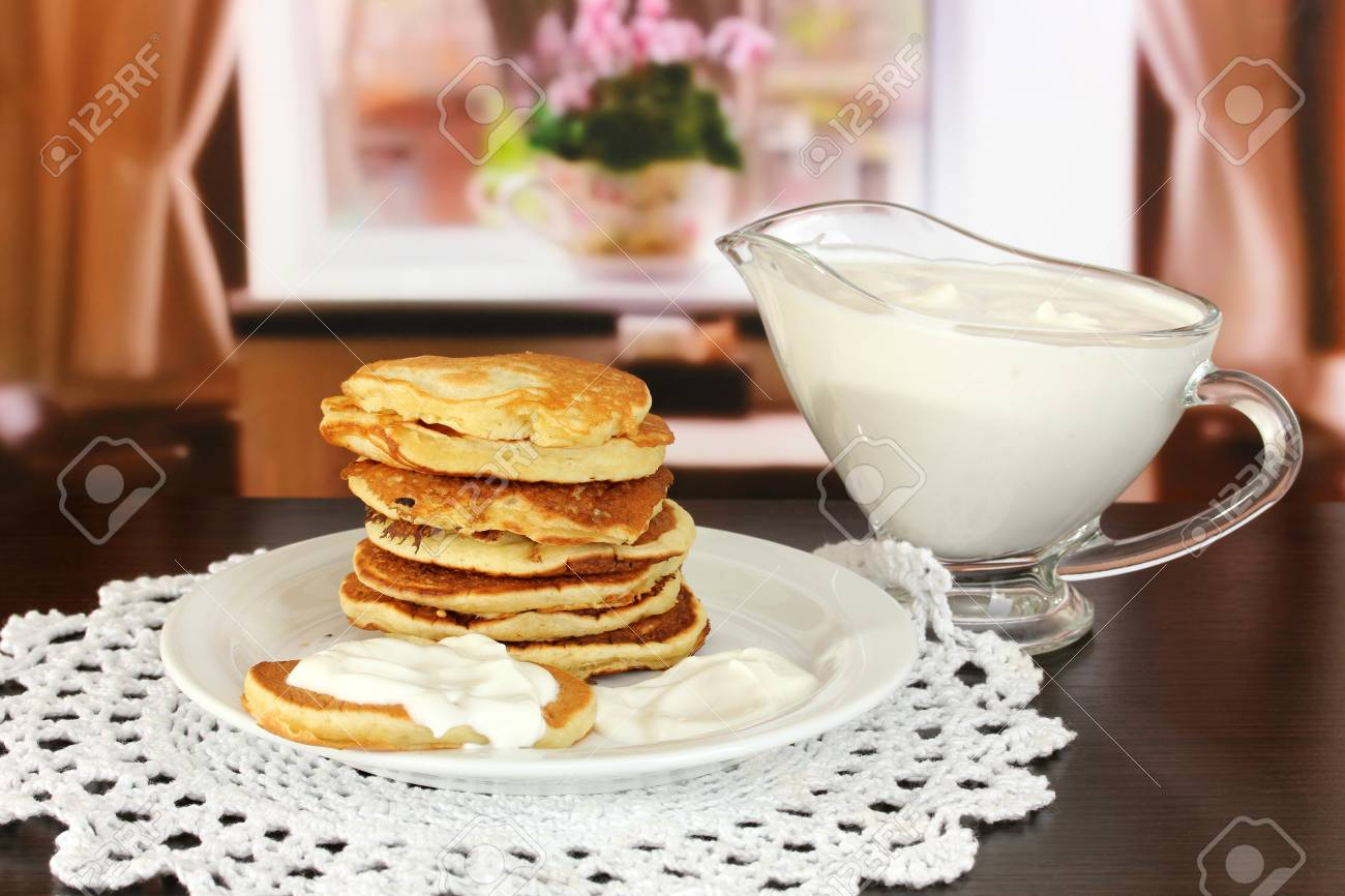 Sweet pancakes on plate with sour cream on table in room Stock Photo - 17486040