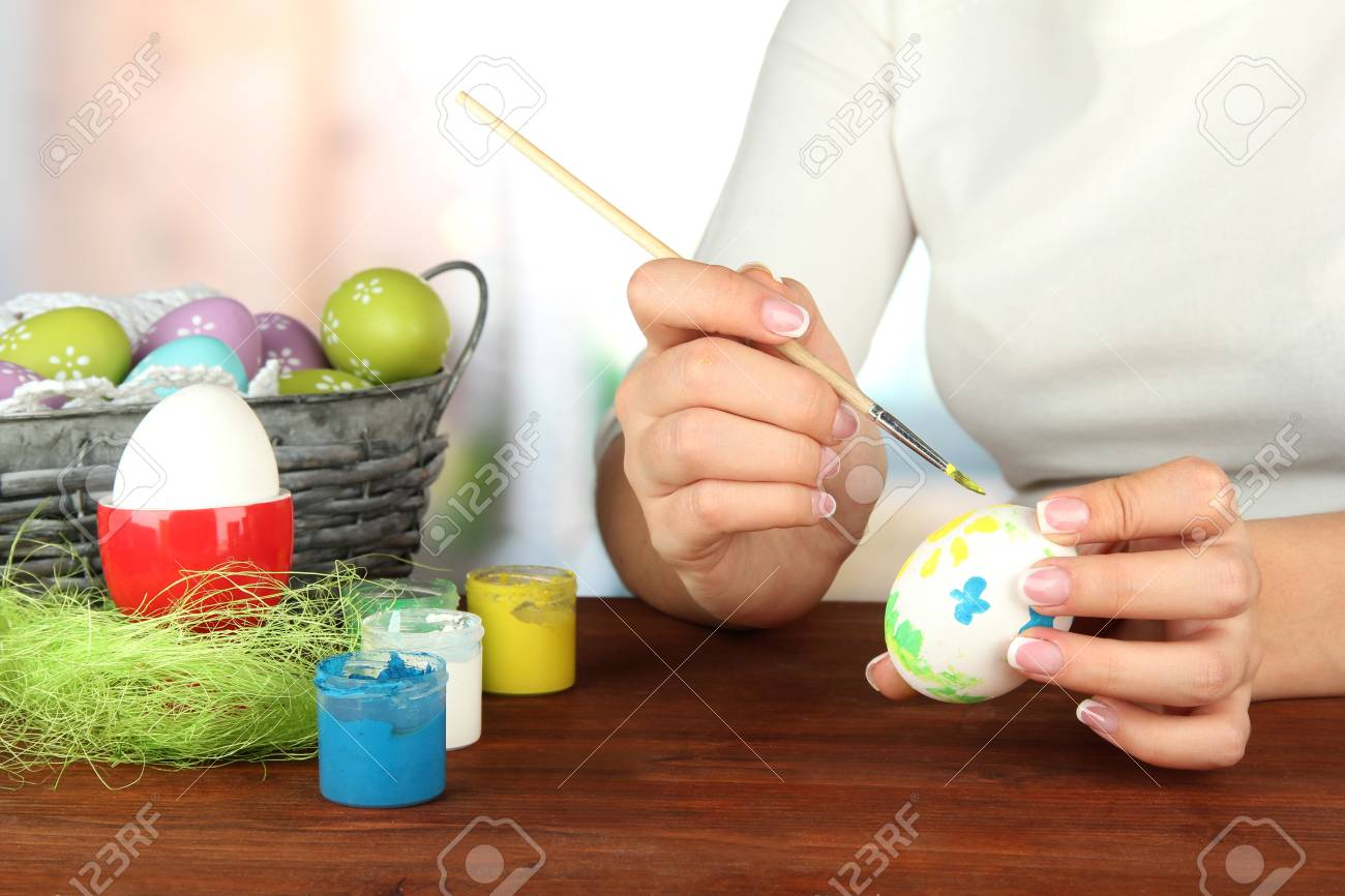 Young woman painting Easter eggs, on bright background Stock Photo - 17518400