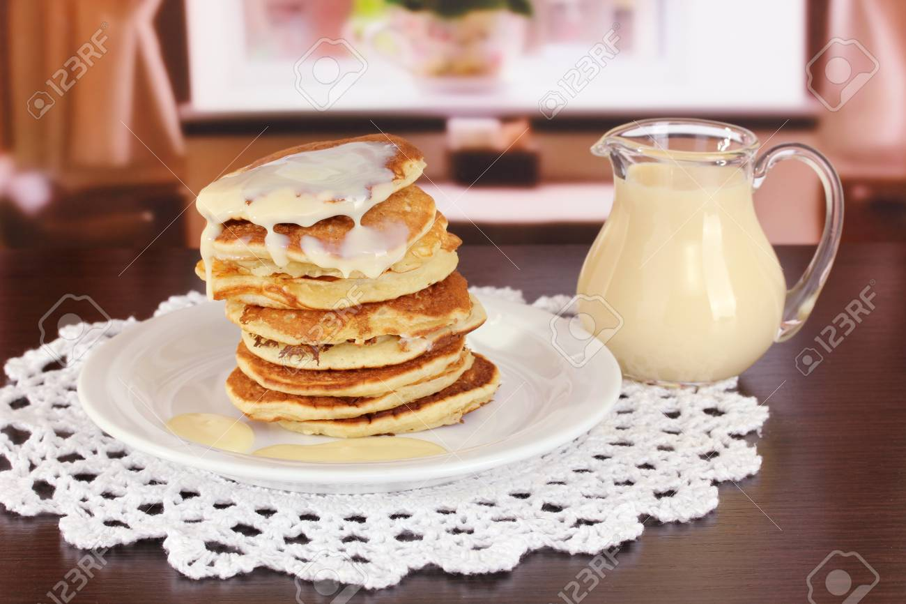 Sweet pancakes on plate with condensed milk on table in room Stock Photo - 17526122