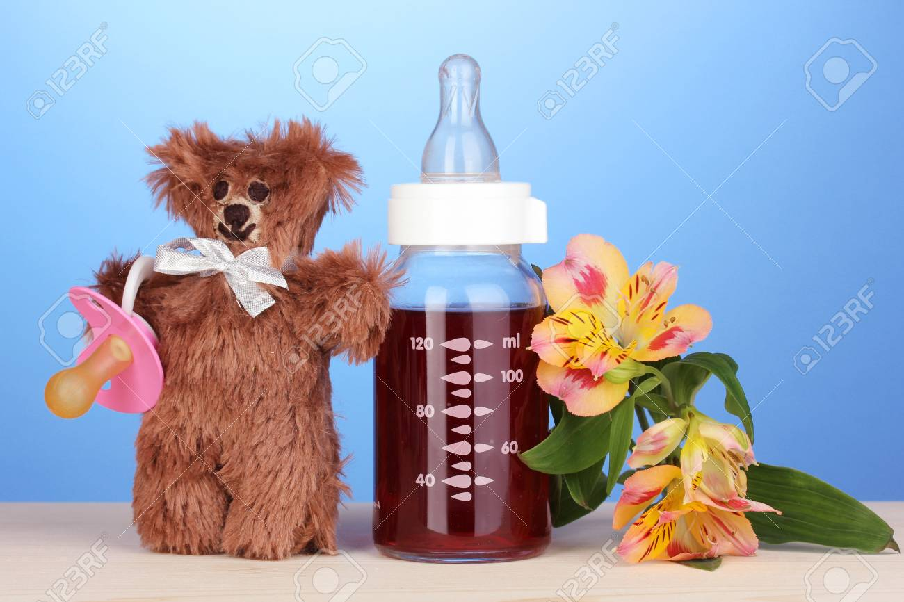 Baby bottle with fresh juice and teddy bear on blue background Stock Photo - 17548400