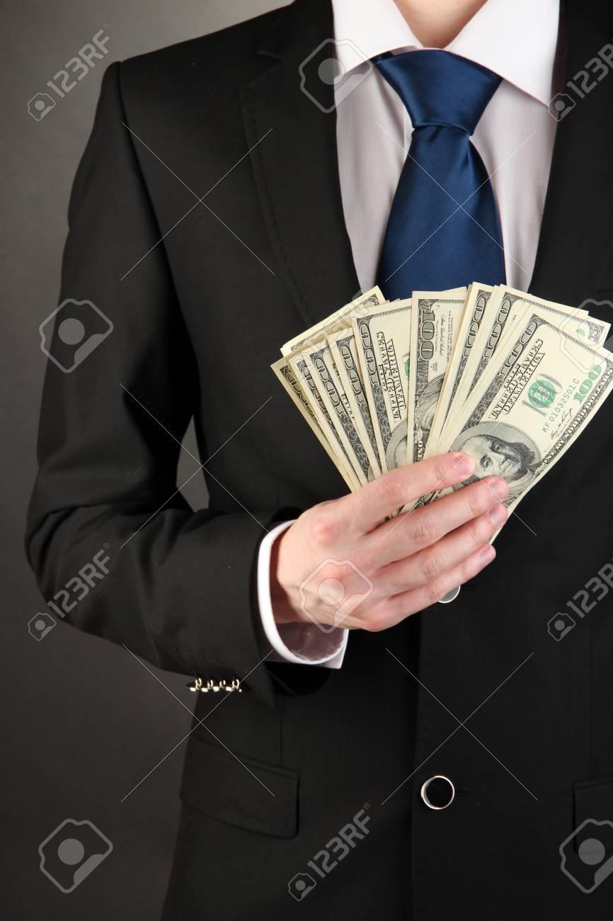 Business man holds lot of money on black background Stock Photo - 17548330