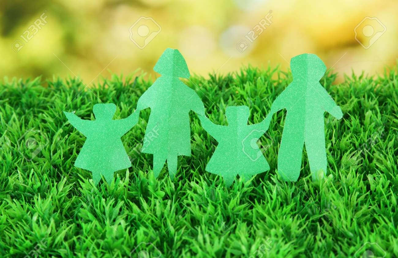Paper people on green grass on bright background Stock Photo - 17634091