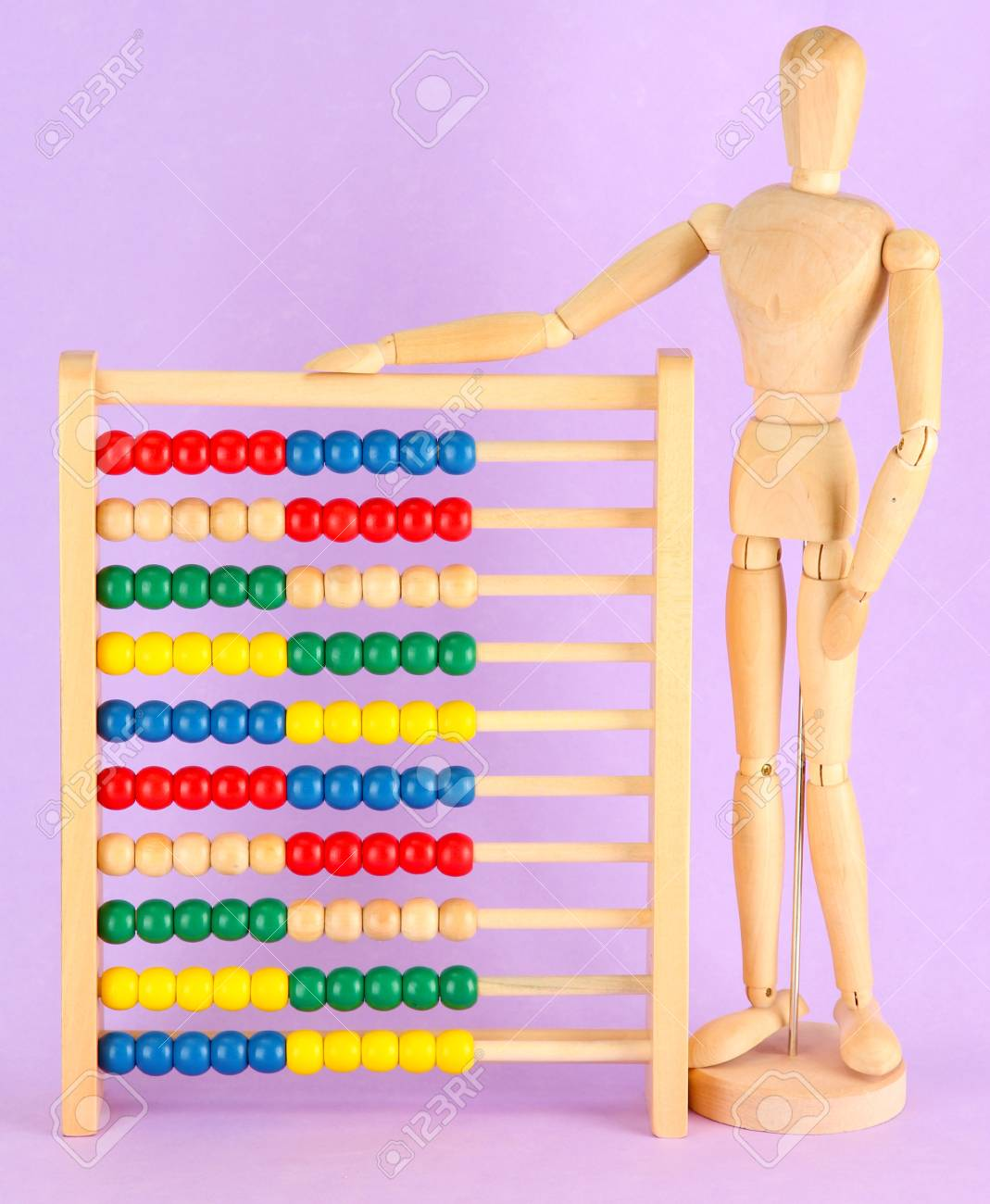 Bright toy abacus and wooden dummy, on purple background Stock Photo - 17760623
