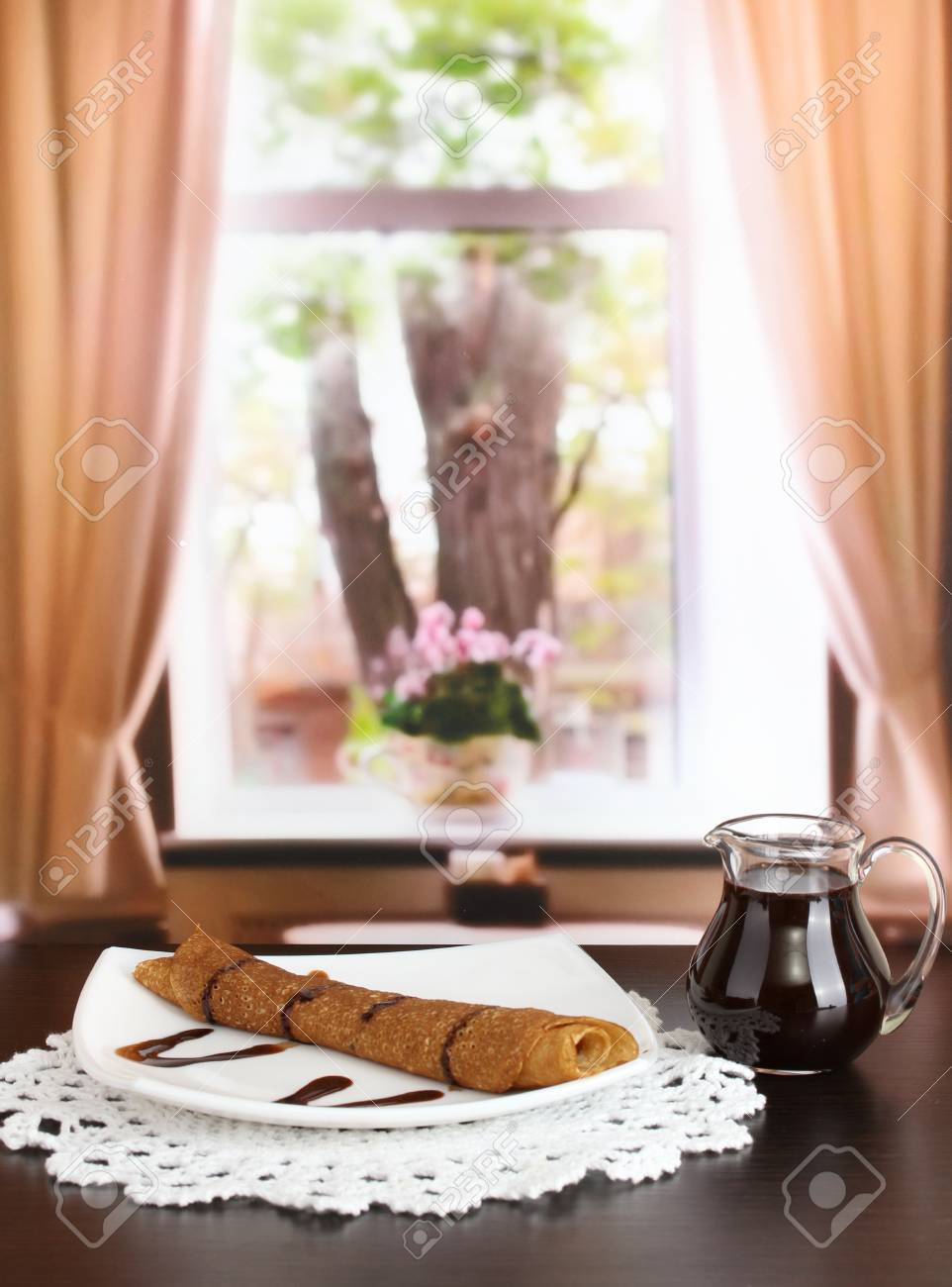 Sweet pancakes on plate with condensed milk on table in room Stock Photo - 17760622