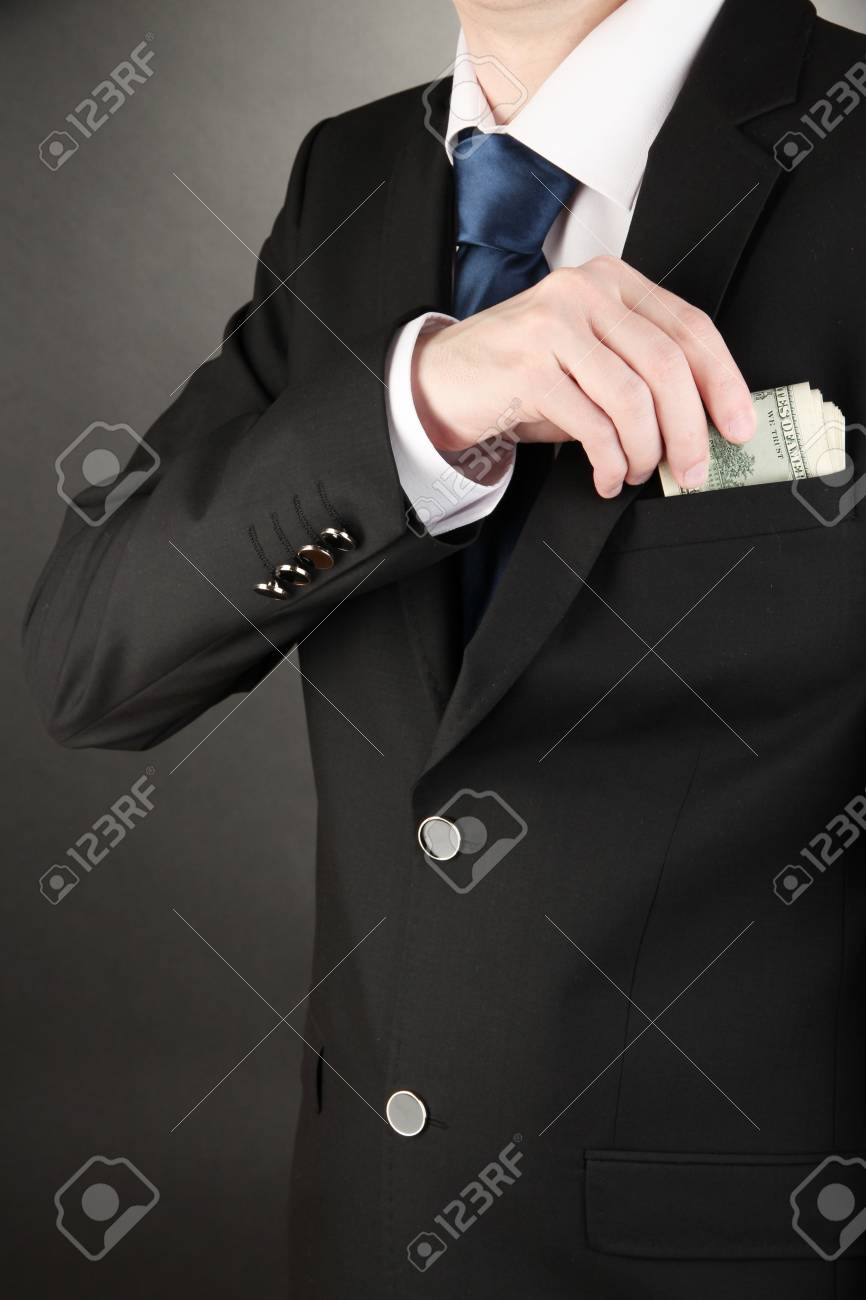 Business man hiding money in pocket on black background Stock Photo - 18143729