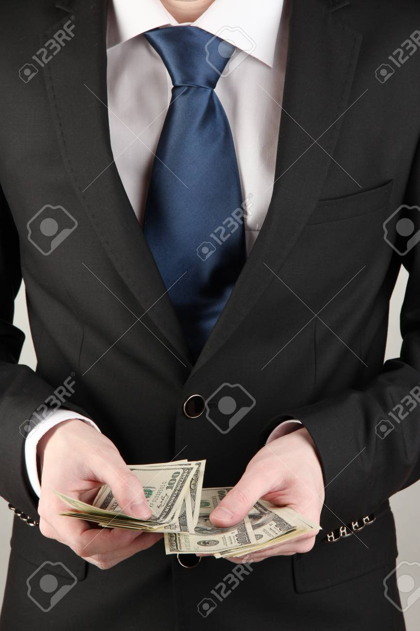 Business man counts money on grey background Stock Photo - 18325655