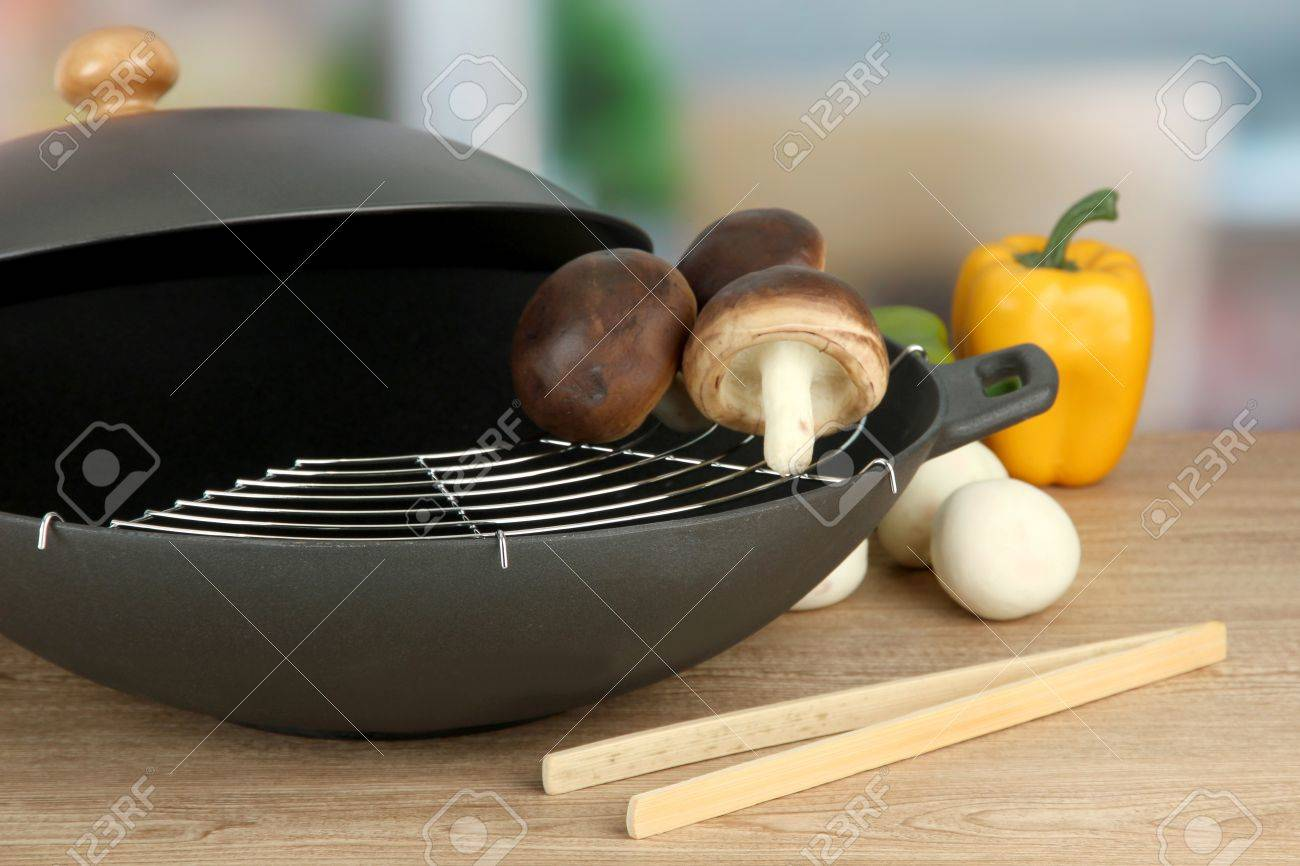 Kitchen Table Close Up black wok pan and vegetables on kitchen table, close up stock