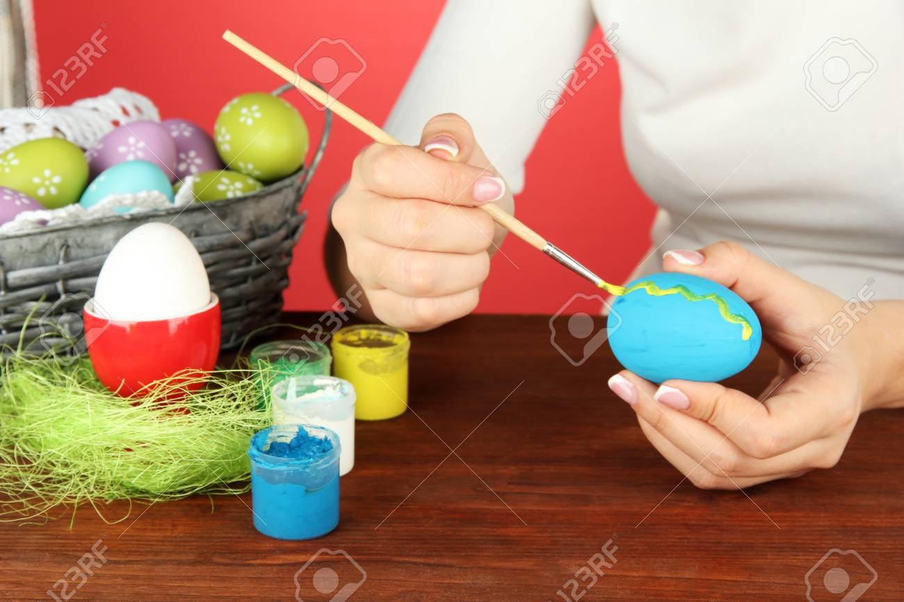 Young woman painting Easter eggs, on color background Stock Photo - 18326373