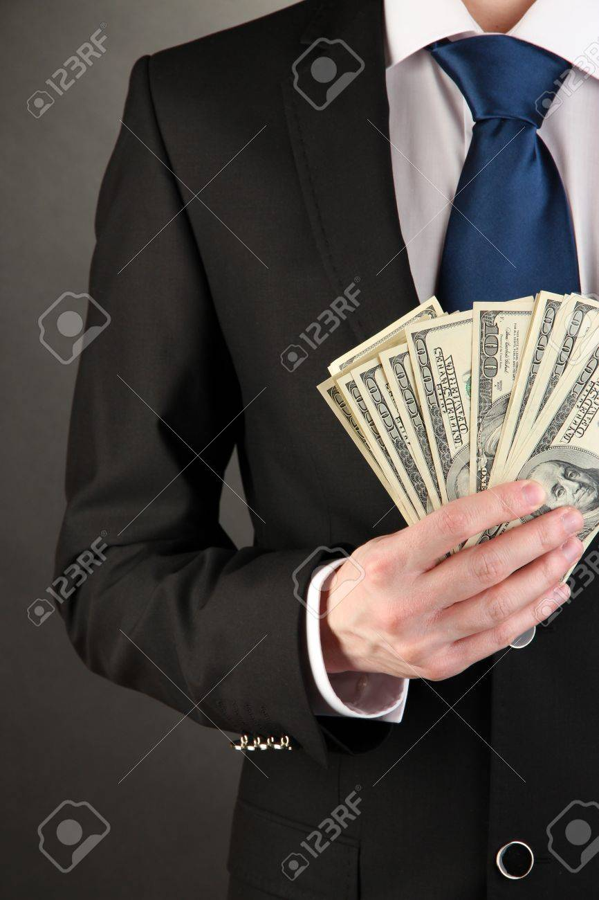 Business man holds lot of money on black background Stock Photo - 18475066