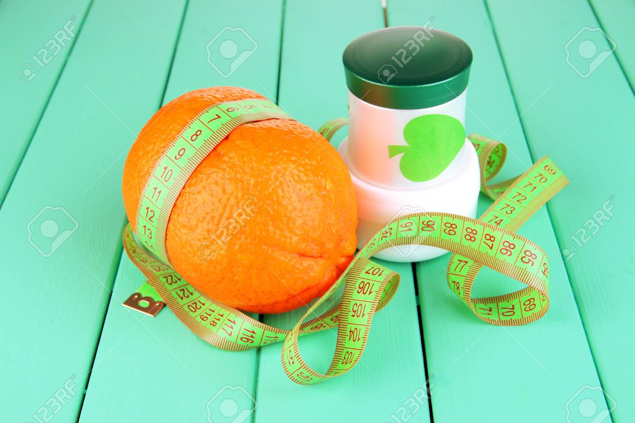 Orange with measuring tape and body cream, on color wooden background Stock Photo - 18507417