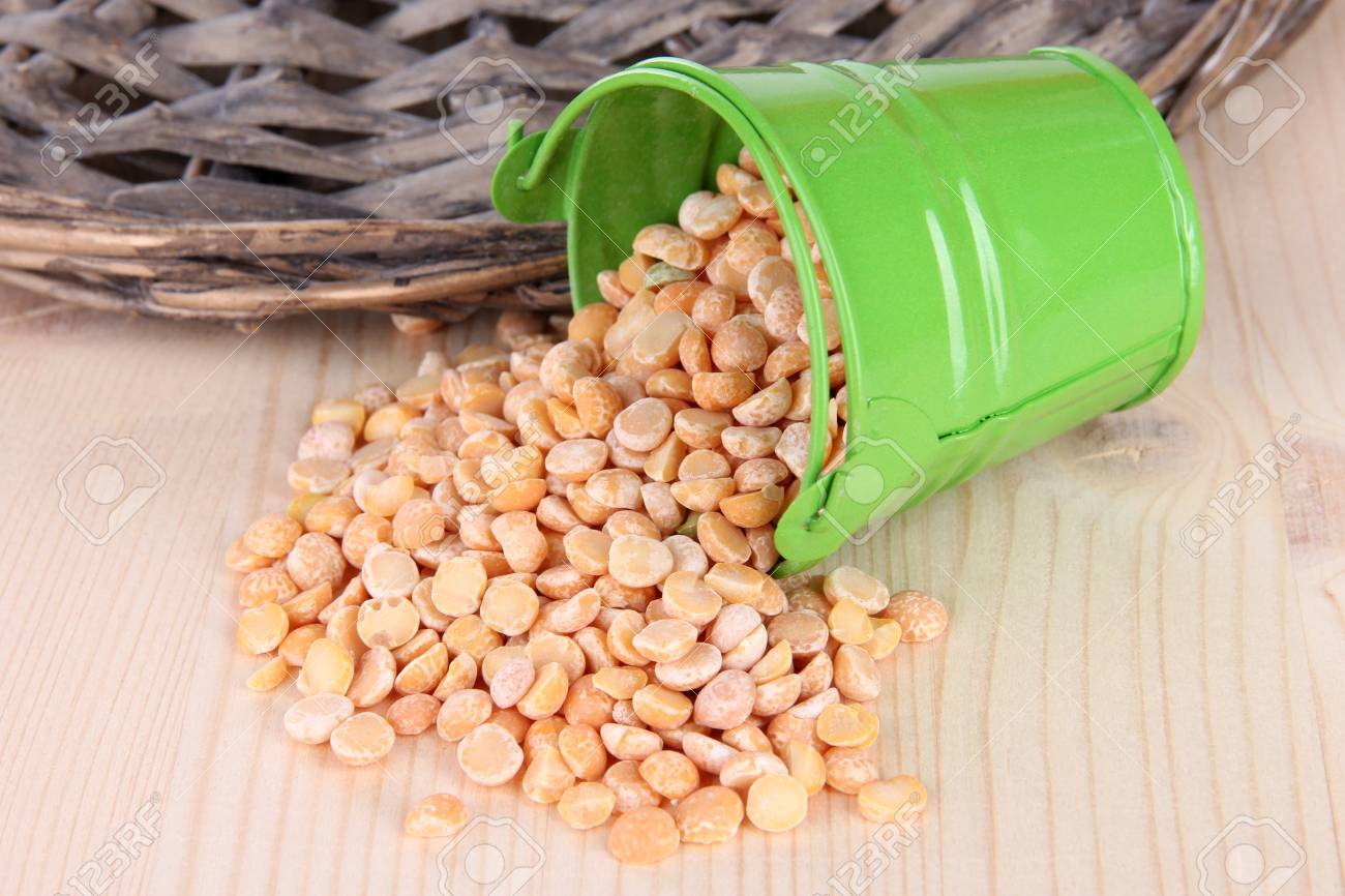Overturned bucket with grains on wooden background Stock Photo - 18849988