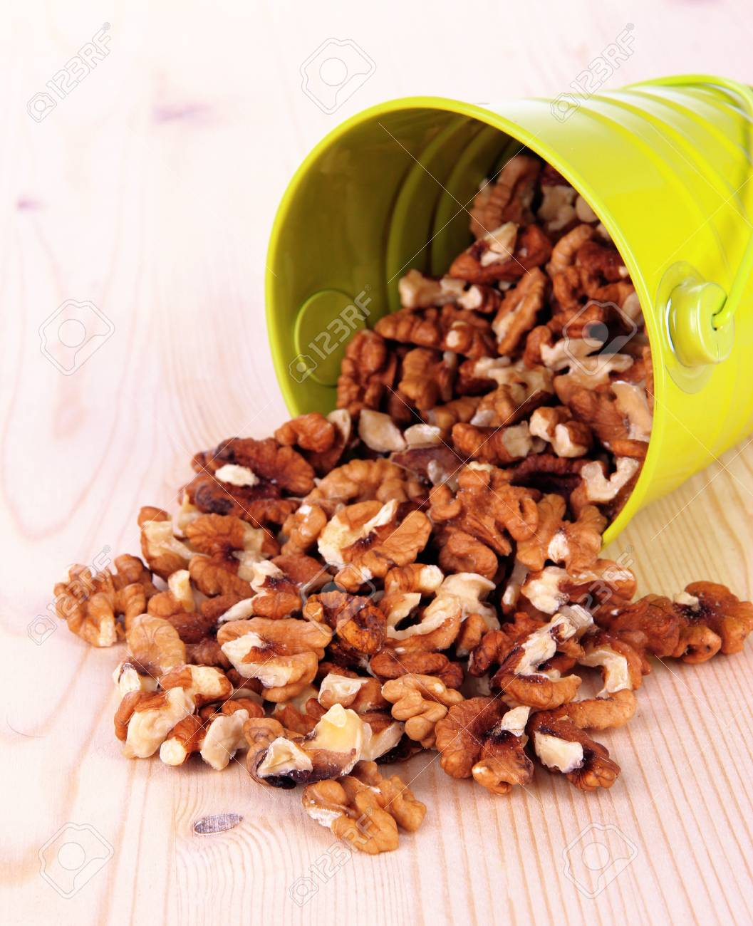 Overturned bucket with nuts on wooden background Stock Photo - 18849365