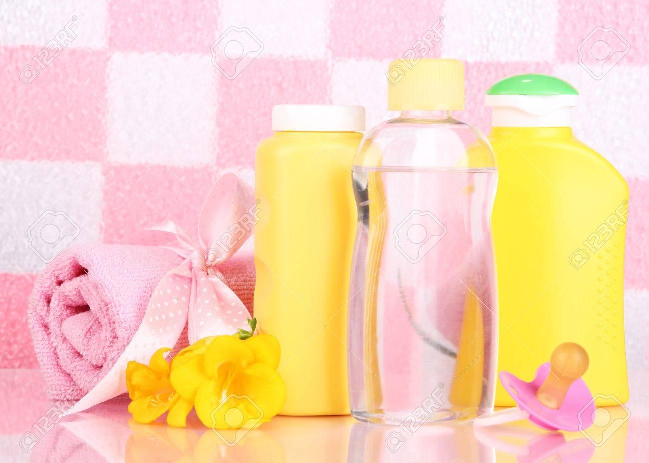 baby-kosmetik und handtuch im badezimmer auf rosa fliesen wand, Hause ideen