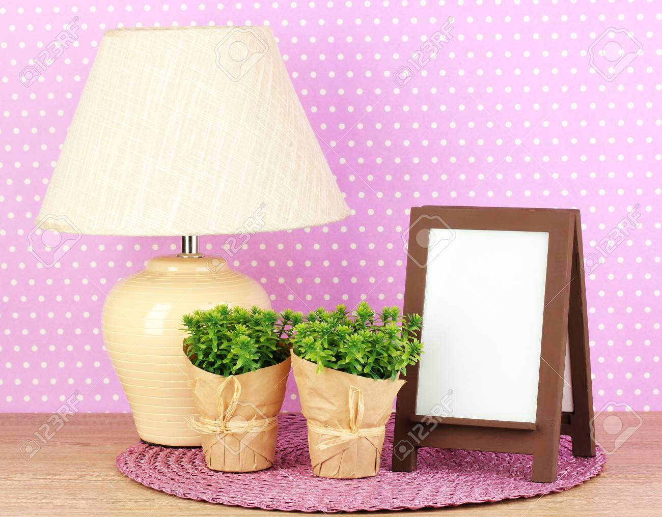 Brown photo frame and lamp on wooden table on lilac wall background Stock Photo - 19046936
