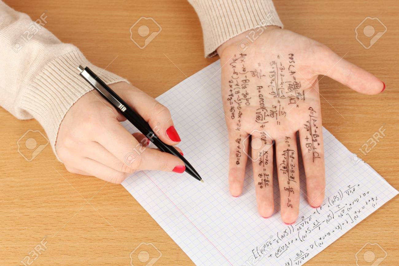 Write cheat sheet on hand on wooden table close-up Stock Photo - 19056293
