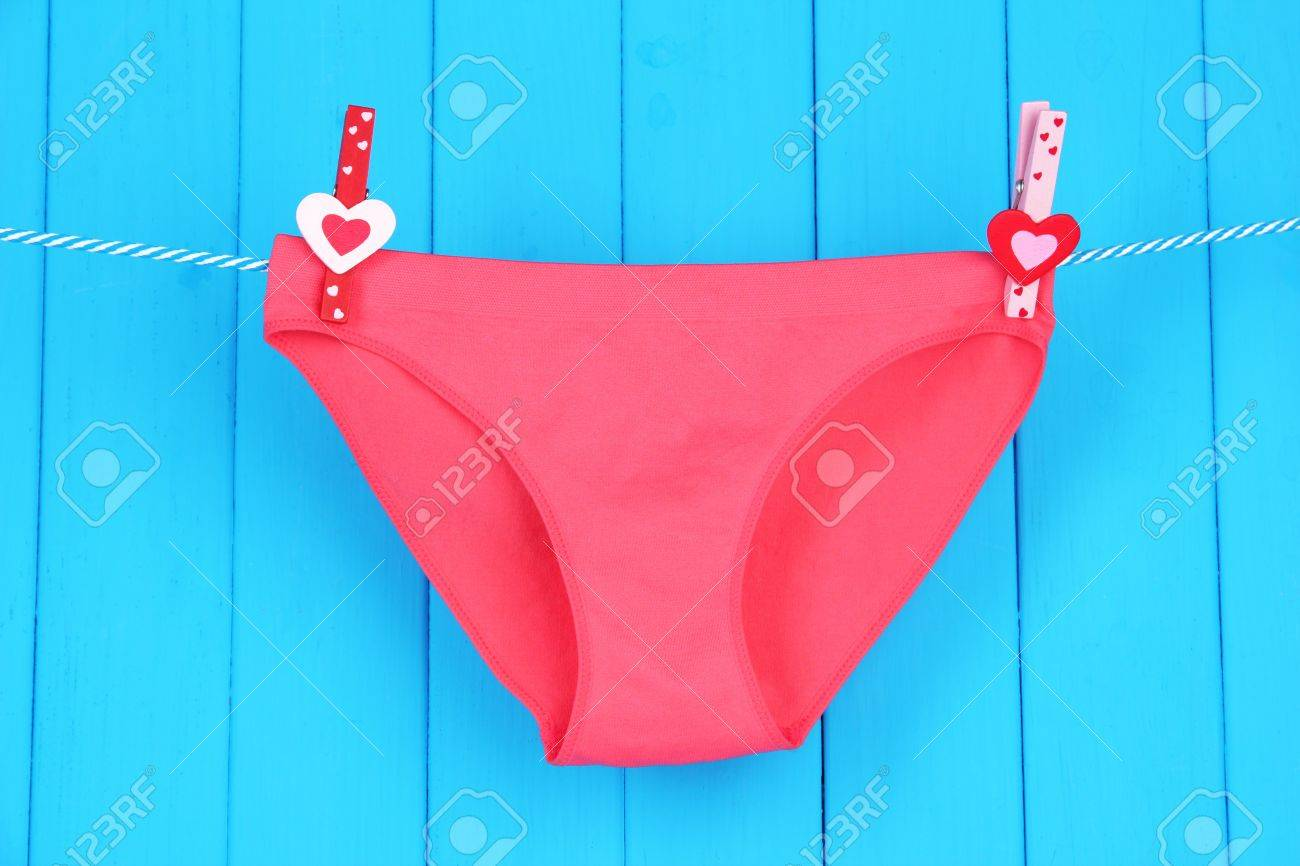 637ea70ccba8 Stock Photo - Womans panties hanging on a clothesline, on blue wooden  background