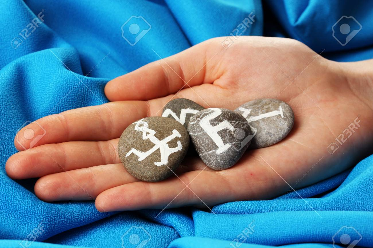 Fortune telling  with symbols on stone in hand on blue fabric background Stock Photo - 19654334