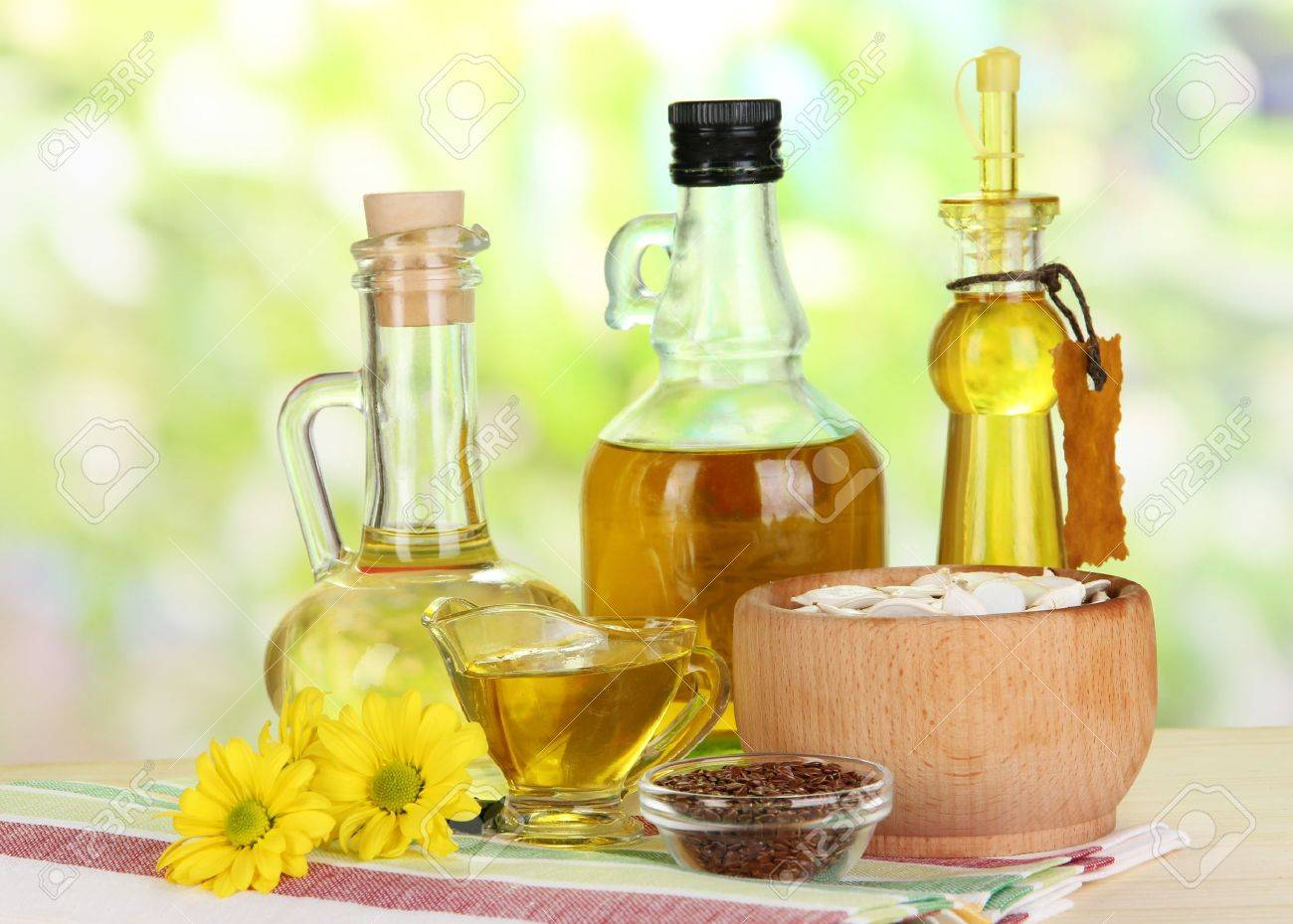Useful linseed oil and pumpkin seed oil on wooden table on natural background Stock Photo - 19763858