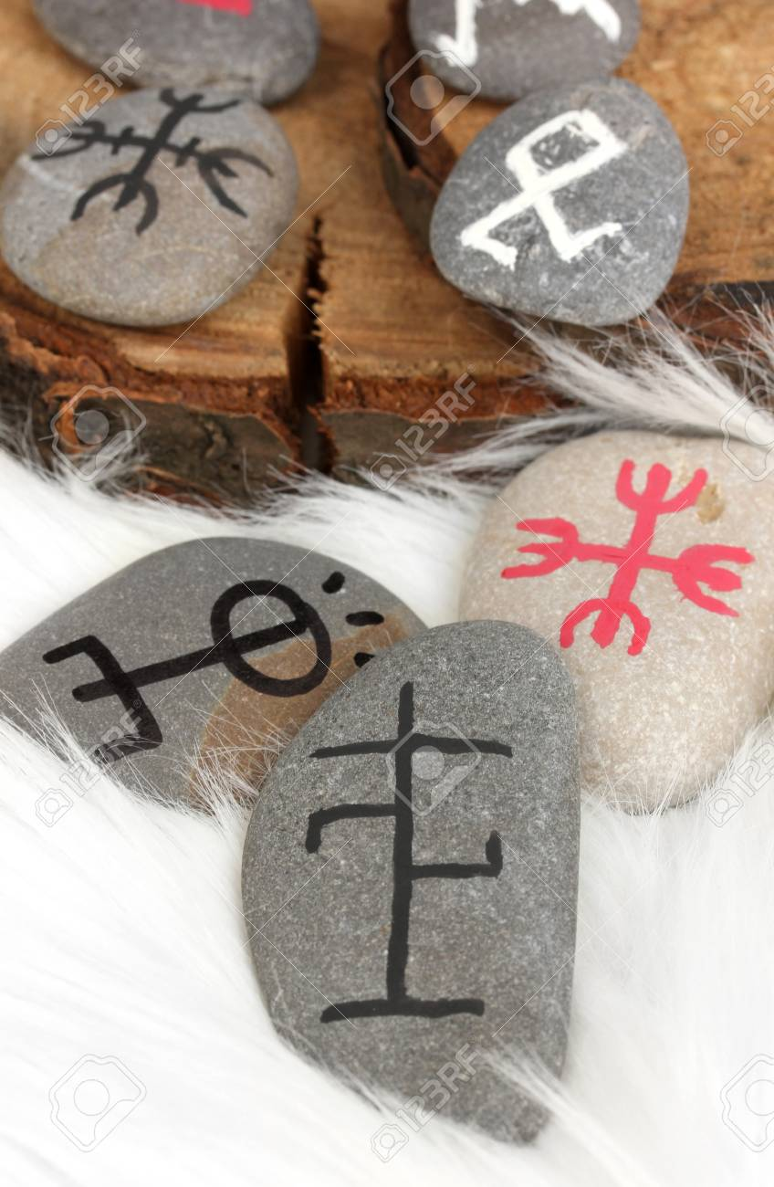 Fortune telling  with symbols on stones on white fur background Stock Photo - 19785741