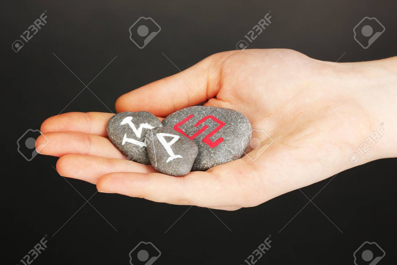 Fortune telling  with symbols on stone in hand on grey background Stock Photo - 19785917