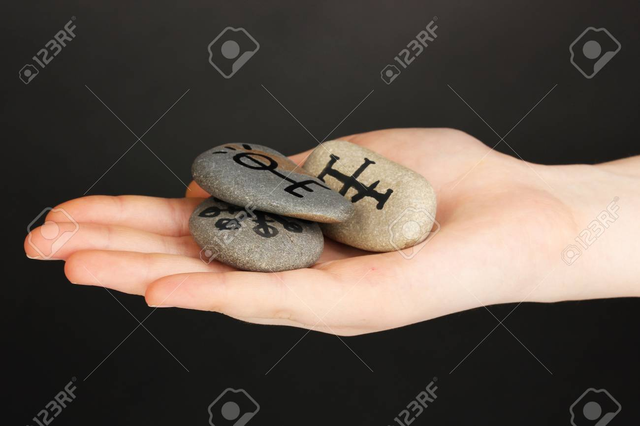 Fortune telling  with symbols on stone in hand on grey background Stock Photo - 20007602