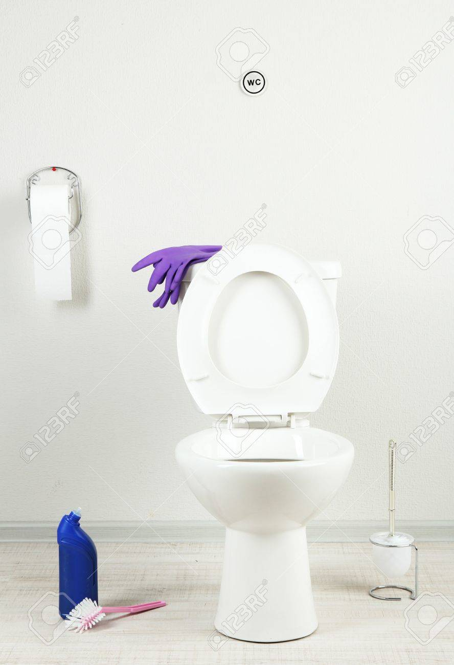 White Toilet Bowl And Cleaner Bottle In A Bathroom Stock Photo