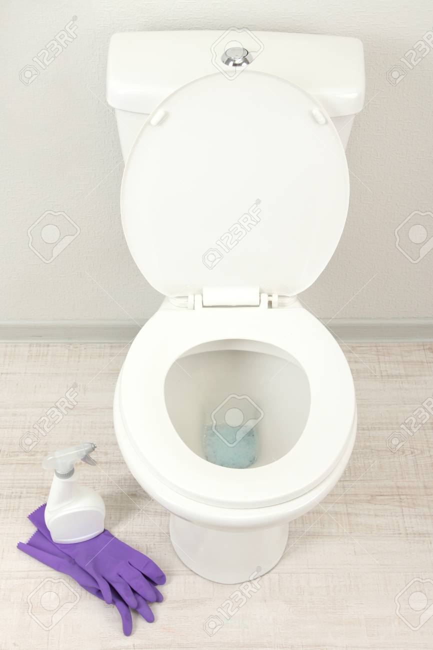 Woman Hand With Spray Bottle Cleaning A Toilet Bowl In A Bathroom ...
