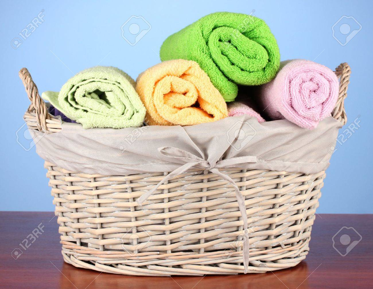 Colorful towels in basket on color background Stock Photo - 20504605
