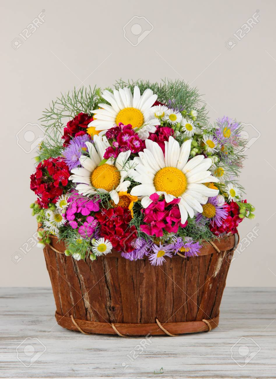 Beautiful Bright Flowers In Wooden Basket On Table On Gray