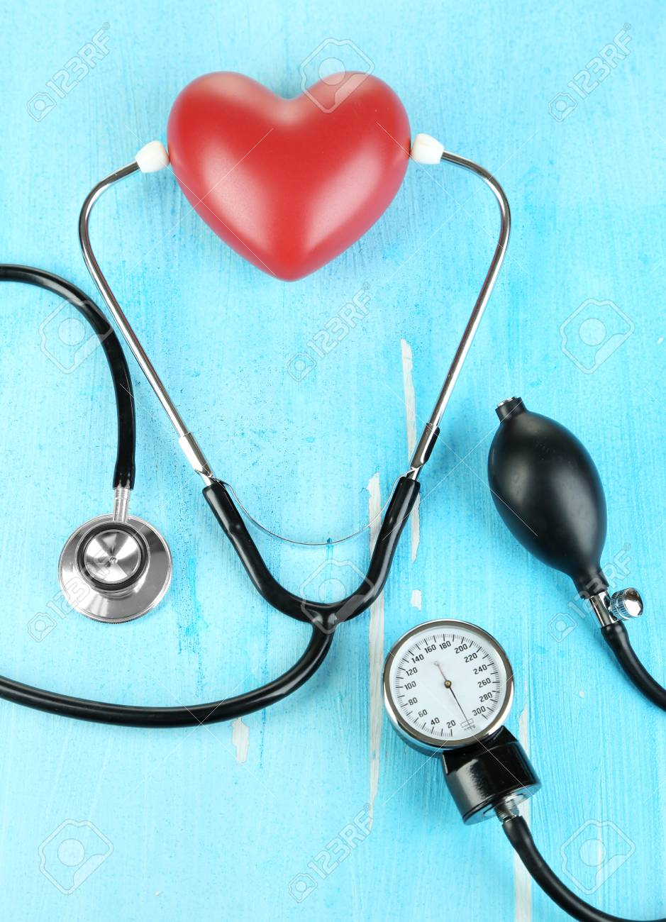 Tonometer, stethoscope and heart on wooden table close-up Stock Photo - 22323214