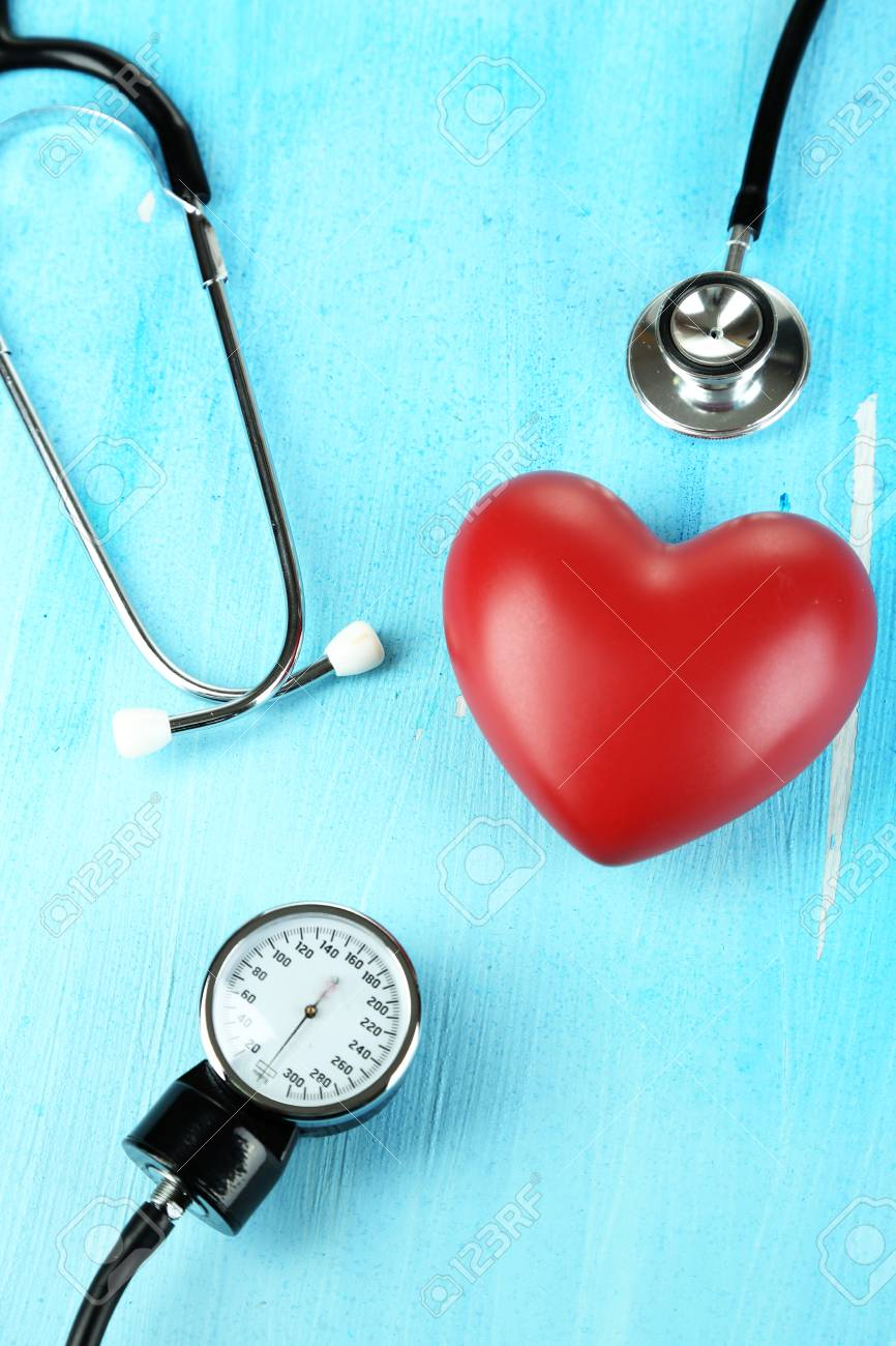Tonometer, stethoscope and heart on wooden table close-up Stock Photo - 22797174